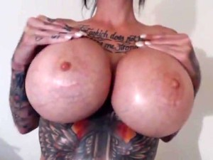 Busty Tatted Brunette Teases With Toy