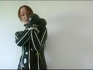 Redhead In Heavy Rubber And Metal Cuffs